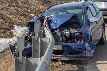 street lighting. the blue car crashed into a metal fence. Close-up. Фото со стока