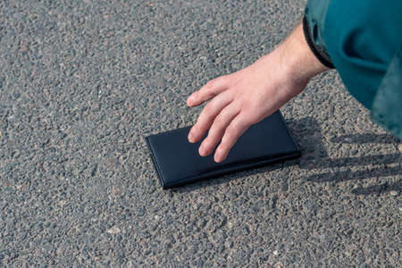 Street lighting. there is a wallet on the road on a sunny summer day. A human hand reaches out to him