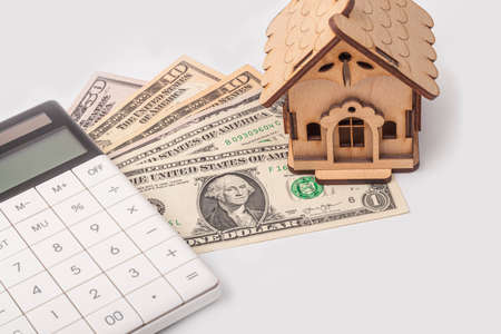 money, dollars, white calculator, toy house concept of buying and maintaining a house, apartment, credit relations, loan0,