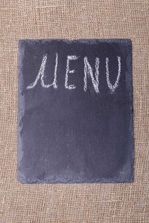 menu. an inscription on a black stone in white chalk. taken on burlap