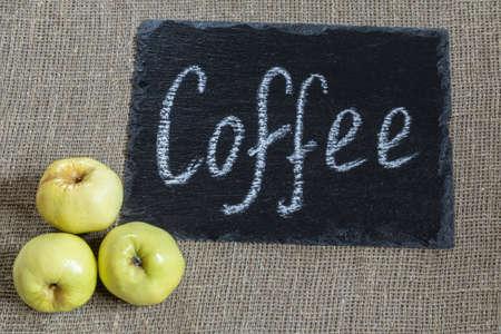 coffee. an inscription on a black stone in white chalk. taken on a burlap bag next to three yellow apples Фото со стока
