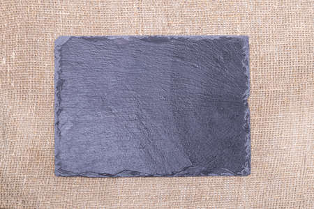 burlap fabric. studio lighting. natural fiber. texture. on it is a black stone in the shape of a square for nadrisi. blank close-up, Фото со стока