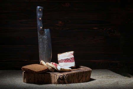 dark background. round wooden tub in retro style. a piece of bacon is cut into pieces. a sharp knife made of forged steel. black bread.