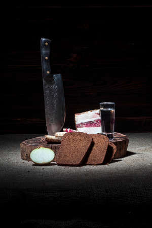dark background. round wooden bathtub in retro style. a piece of bacon is cut into pieces. a sharp knife made of forged steel. black bread, a head of onion and a glass of vodka