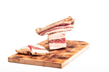 wooden board in retro style. a piece of bacon is cut into pieces on it. on a white background. close-up Фото со стока