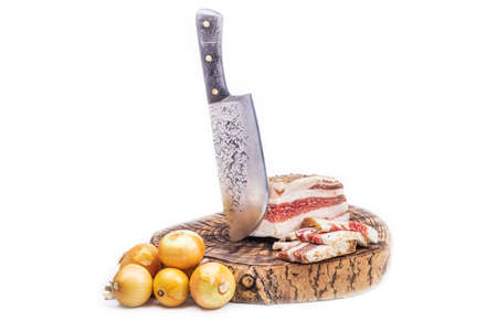 wooden stand. a sharp knife in retro style. a piece of delicious bacon and a slice is cut next to it. the golden yellow heads of the bulbs lie next to each other. on a white background. Фото со стока