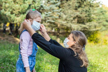 natural light. mom puts on a medical mask for a child with white hair.