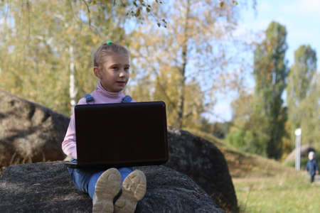 street lighting. a girl with white hair is engaged in the open air. in the hands of a laptop. remote classes in the pereud pendemia.