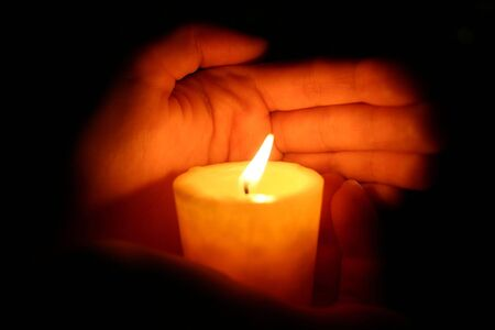 hands keeps burninging candle in the dark photo