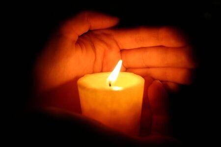 mano de dios: manos mantiene burninging vela en la oscuridad
