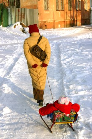 woman carries child in sled photo