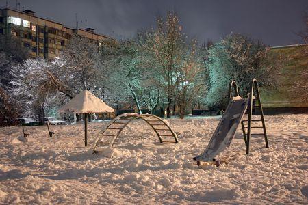 snow-clad playground, winter, evening, unusual illumination,