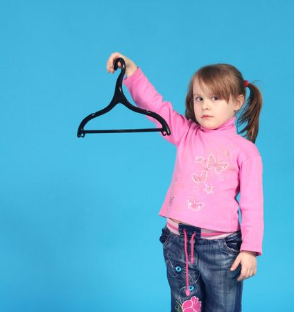 child keeps clothes hanger, blue background photo