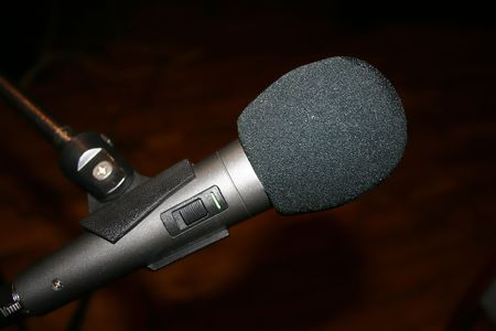 gray microphone on stand, brown background