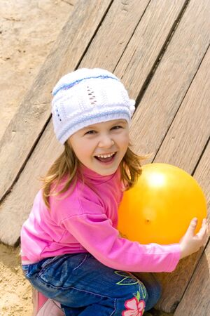 The child on a playground holds a yellow ball Stock Photo
