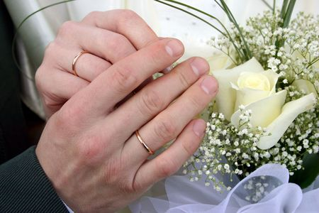 Two rings on fingers newly married, a bouquet of yellow roses in a hand photo