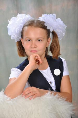 mo�o blanco: La colegiala en un uniforme escolar con un lazo blanco y una insignia