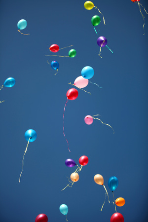 The multi-colored balloons departing to the blue sky