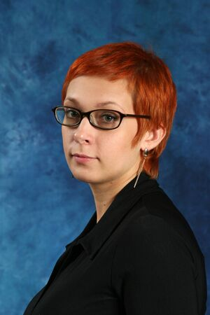 the girl with red hair, wearing spectacles in a black frame Stock Photo