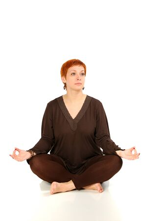 The girl with red hair meditates on a white background