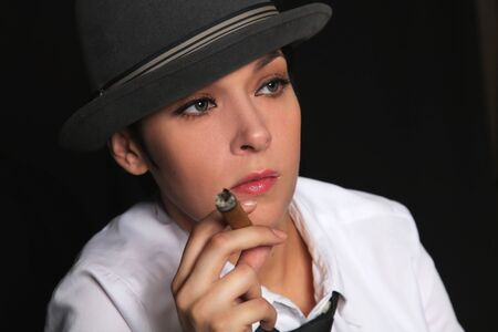 the girl in a hat and a white shirt keeps in fingers a cigar photo