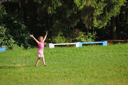The cheerful girl in pink clothes on a summer meadow Stock Photo