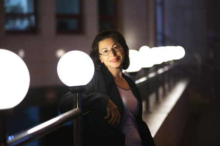 The adult woman in a black jacket. Evening, light from a round lamp Stock Photo