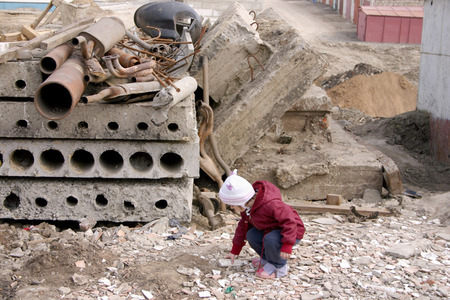 The little girl lifts a stone fragment against construction garbage