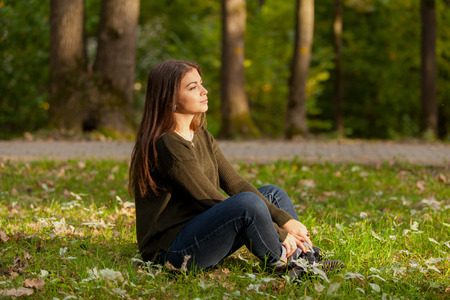 The young beautiful girl with long hair, meditates in autumn park