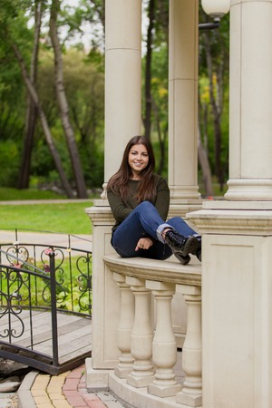arbour: The beautiful girl on an arbour handrail in autumn park