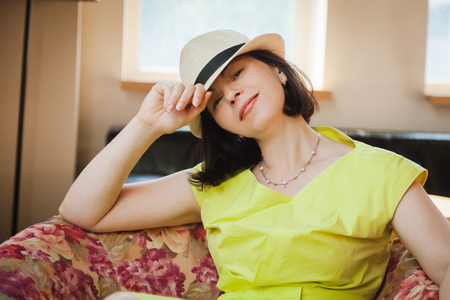 beautiful woman in a yellow dress and hat