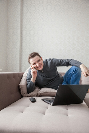 The man on a sofa with laptop and mobile phone Stock Photo