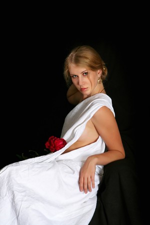 The girl who is wrapped up by white fabric on a black background with  rose Stock Photo