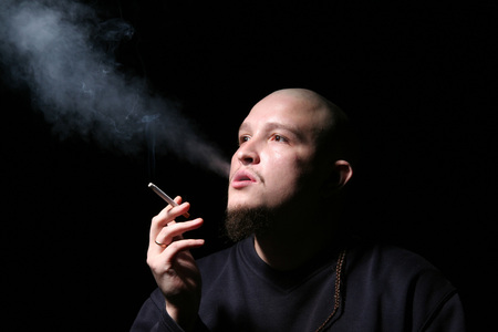 The bald man with a cigarette smokes in dark Stock Photo