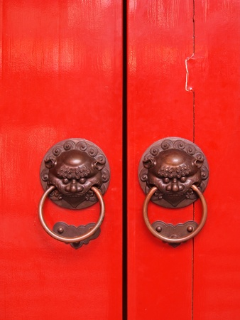 Red chinese door with a lion/dragon head.