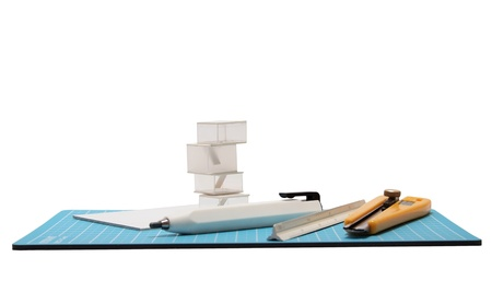 Cutter,pencil,scale and architectural model placed on blue cutting mat.       photo