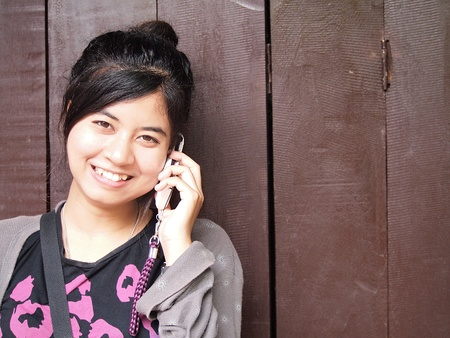 happy smiling teenage girl with the mobile phone  on wood background        photo