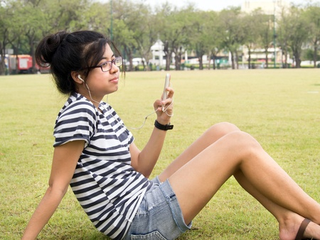 A young girl with headphones outdoors. Listening music Stock Photo - 13053224