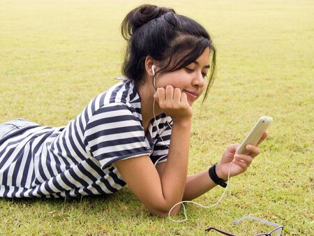 Woman relaxing and listening to music outdoors  Stock Photo - 13053235