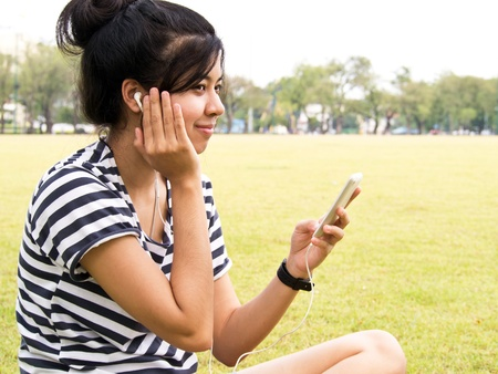 A young girl with headphones outdoors. Listening music  Stock Photo - 13053205