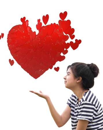 Romantic young woman holding a big heart composed of small red hearts in hands