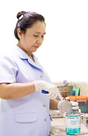 Female nurse open alcohol bottle on white background. Stock Photo - 13228285