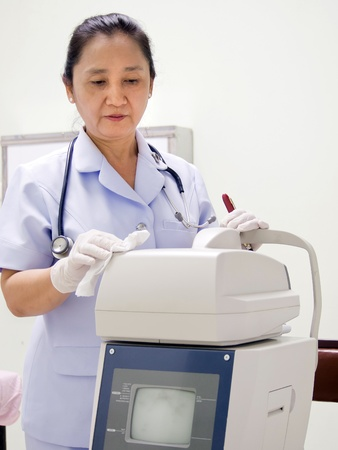 Nurse Cleaning Hospital Equipment; Computerized Optometer Stock Photo