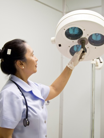 Nurse with surgical lamp in operation room photo