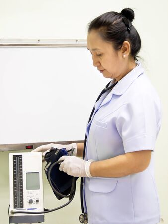 Nurse with blood pressure meter photo