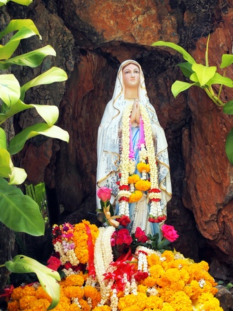 Virgin mary statue with garlands in cave. Stock Photo