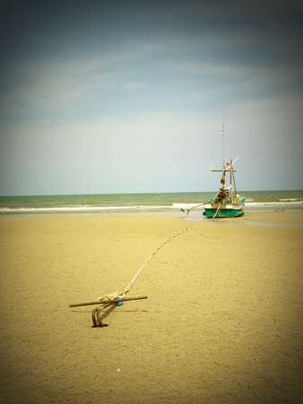 A fishing boat anchored by the beach, retro style photo