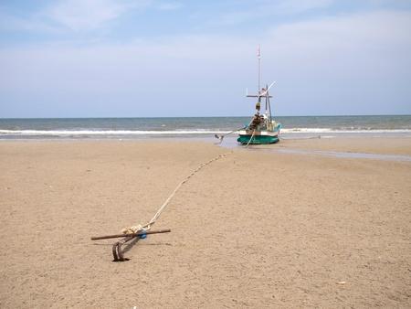 A fishing boat anchored by the beach, huahin, thailand photo