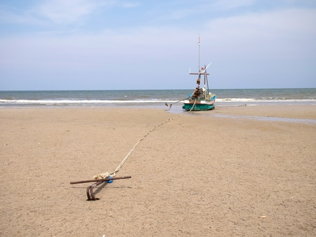 A fishing boat anchored by the beach, huahin, thailand photo