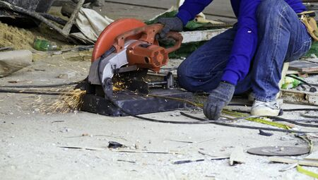 cutoff: Worker in workwear cutting metal reinforcing bar with abrasive cutoff saw disk